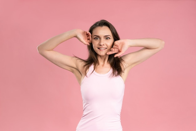 Charmante junge frau, die hände ohne make-up, hautpflegekonzept, attraktives brünettes mädchen im rosa t-shirt hochhält.
