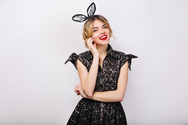 Charmante junge frau, die schwarzes kleid und schwarze krone trägt, feiertage feiert, spaß hat, lächelt.