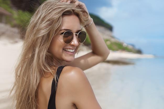 Charmante junge frau, die sommerferien im sonnigen sandstrand genießt