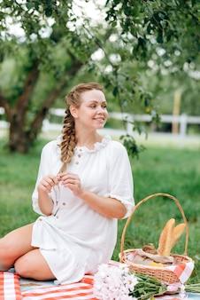 Charmante junge frau, die um ihren picknickkorb sitzt