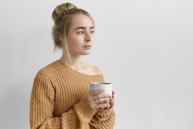 Charmante junge frau, die unordentliche frisur und übergroßen gestrickten pullover trägt, der an grauer leerer wand aufwirft, großen becher hält, tee, kaffee, kakao oder heiße schokolade am morgen trinkt