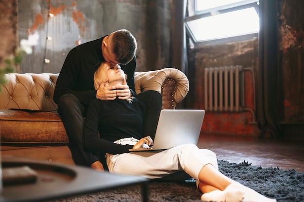 Charmante junge frau, die zu hause an ihrem laptop arbeitet, während sie sich auf ihren freund stützt
