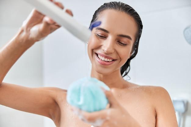Charmante junge frau gießt duschgel auf bad luffa
