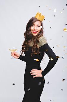 Charmante junge frau im luxuriösen schwarzen kleid, das große neujahrsparty auf weißem raum feiert