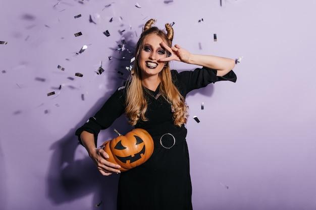 Charmante junge frau im schwarzen kleid, die halloween-karneval genießt. foto des lächelnden vampirmädchens, das orange kürbis hält.