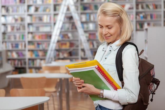 Charmante junge frau in der bibliothek oder im buchladen
