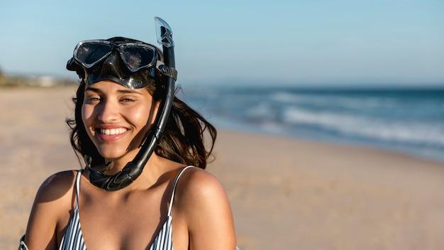 Charmante junge frau in schnorcheln maske am strand