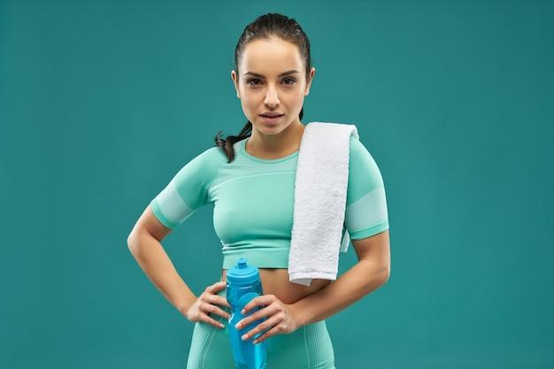 Charmante junge frau in sportkleidung mit einer flasche wasser