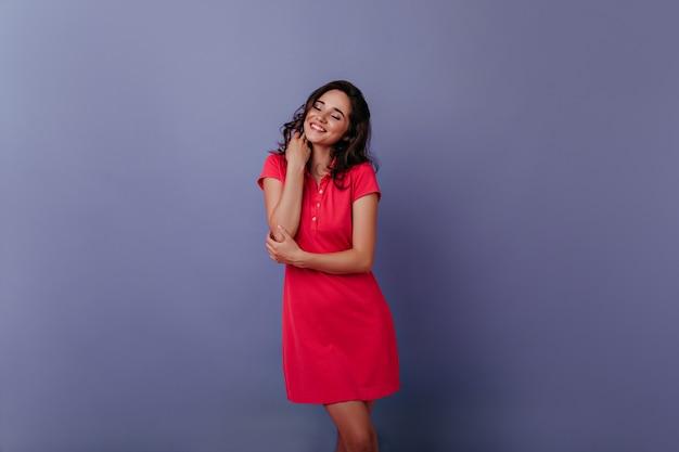 Charmante junge frau lächelnd mit geschlossenen augen auf lila wand. innenfoto des blithesome lockigen mädchens im trendigen roten kleid.