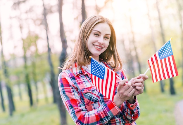 Charmante junge frau mit amerikanischen flaggen