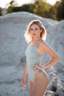 Charmante junge frau mit blonden haaren, die unter leerem sandsteinbruch in nur badeanzug steht. sonniges warmes wetter im freien. sommersaison.