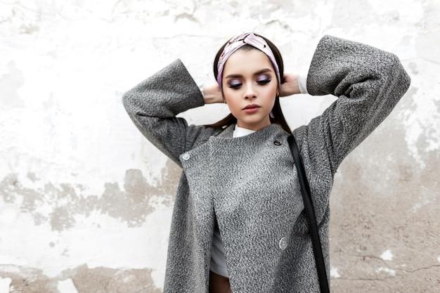 Charmante junge frau mit farbigem make-up in modischer oberbekleidung glättet das haar. schönes mädchen im vintage-bandana im grauen trendigen mantel mit lederhandtasche posiert in der nähe des gebäudes auf der straße.