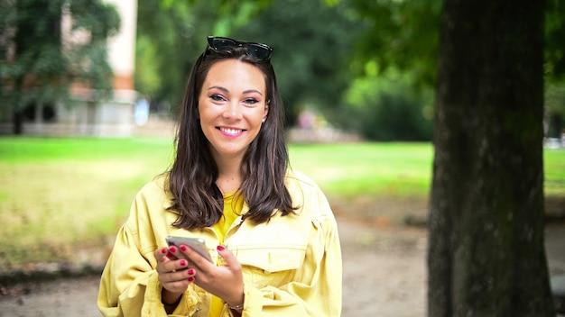 Charmante junge frau mit ihrem smartphone im park und lachen