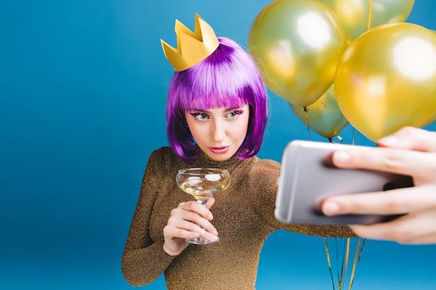 Charmante junge frau mit lila haarschnitt, krone auf kopf machen selfie-porträt. goldene luftballons, champagner, neujahrsparty, luxuskleid, lametta-make-up.
