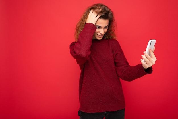 Charmante junge frau mit lockigem haar, das dunkelroten pullover trägt, lokalisiert auf roter hintergrundwand