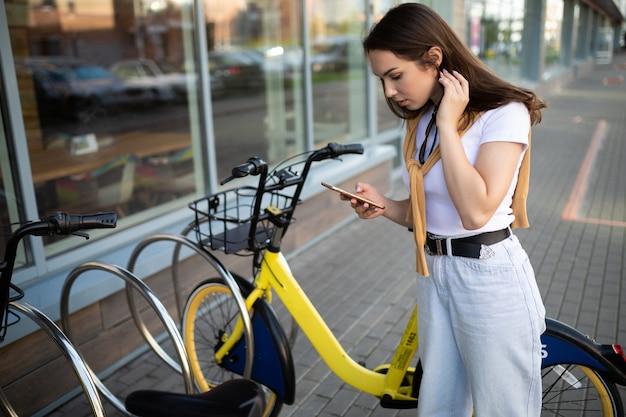 Charmante junge frau sitzt hinter dem lenkrad, das in der bewerbung bezahlt wurde