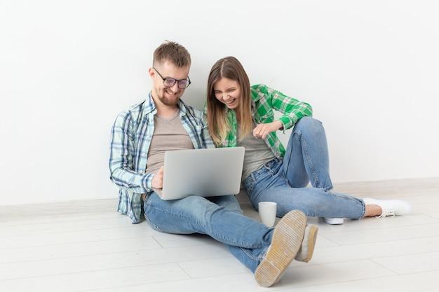 Charmante junge frau und ein lächelnder mann beobachten online-shops mit einem laptop, um klempnerarbeiten zu kaufen