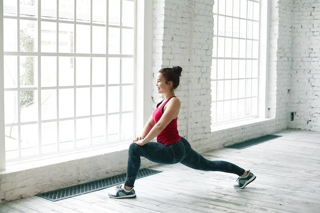 Charmante junge kaukasische yogalehrerin mit haarknoten, die die beine vor dem unterricht im fitnesscenter aufwärmt und fröhlich lächelt, während sie eine hohe longe-pose macht. nettes mädchen, das tagsüber drinnen trainiert