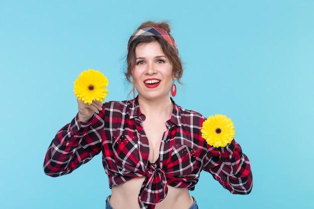 Charmante junge lächelnde frau mit zwei roten und orangefarbenen blumen in ihren händen posiert auf blauem hintergrund. konzept der schönheit und selbstpflege. platz für werbung