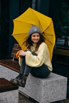 Charmante junge lockige frau, die auf bank sitzt und gelben regenschirm an der straße von megapolis-stadt in regnerischem tag verwendet