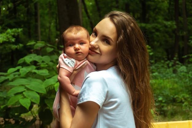 Charmante junge mutter mit kleinem baby in den händen