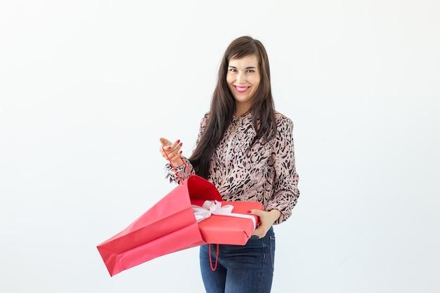 Charmante junge positive brünette frau, die eine tasche mit geschenkbox hält, die gegen ein weiß aufwirft