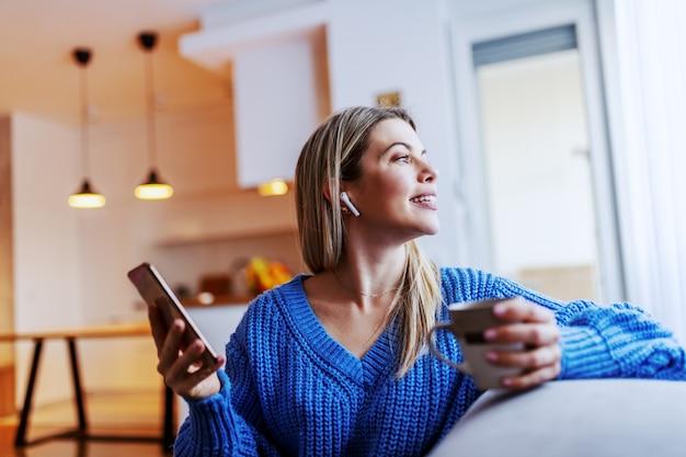 Charmante kaukasische blonde frau, die im wohnzimmer auf sofa sitzt, tasse kaffee und smartphone hält und durch fenster schaut.