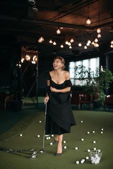 Charmante kaukasische dame posiert für die kamera und spielt golf, bild einzeln auf dunklem hintergrundunschärfe