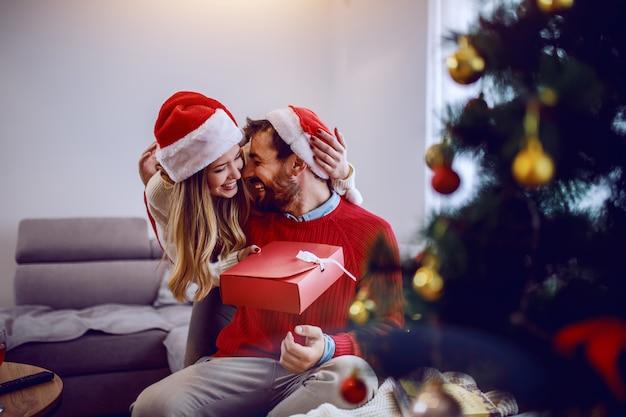 Charmante kaukasische frau, die ihrem freund weihnachtsgeschenk gibt. beide tragen pullover und weihnachtsmützen auf den köpfen. wohnzimmerinnenraum, weihnachtsferienkonzept.