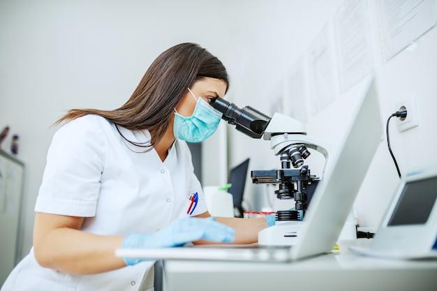 Charmante kaukasische laborassistentin in weißer uniform, mit schutzmaske und gummihandschuhen, die im labor sitzen und blutprobe durch mikroskop suchen und laptop verwenden.