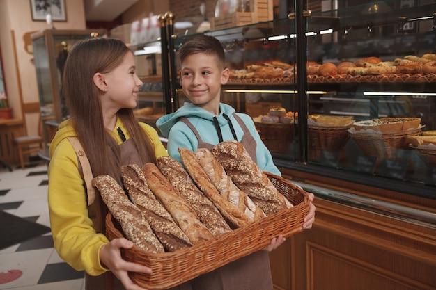 Charmante kleine kinderbäcker, die köstliches brot in ihrem familienbäckerei-café verkaufen
