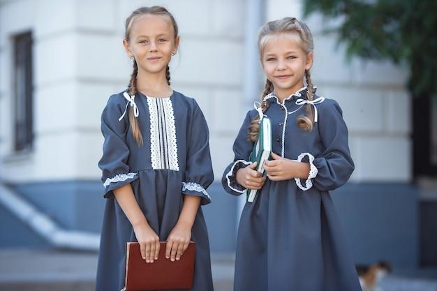 Charmante kleine mädchen im retro-kleid, die an einem sonnigen sommertag in der stadt gehen. Premium Fotos