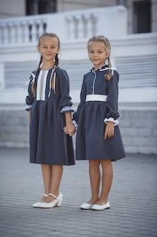 Charmante kleine mädchen im retro-kleid, die an einem sonnigen sommertag in der stadt gehen.