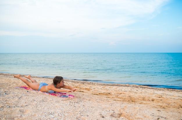 Charmante kleine mädchen machen gymnastikübungen, während sie am strand entspannen