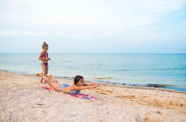 Charmante kleine mädchen machen gymnastikübungen, während sie an einem sonnigen, warmen sommertag am strand entspannen. das konzept von sport und aktiven spielen im sommer. copyspace