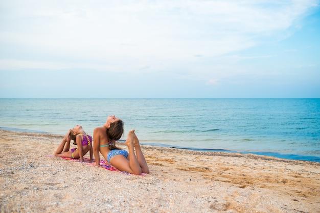 Charmante kleine mädchen machen gymnastikübungen, während sie an einem sonnigen, warmen sommertag am strand entspannen