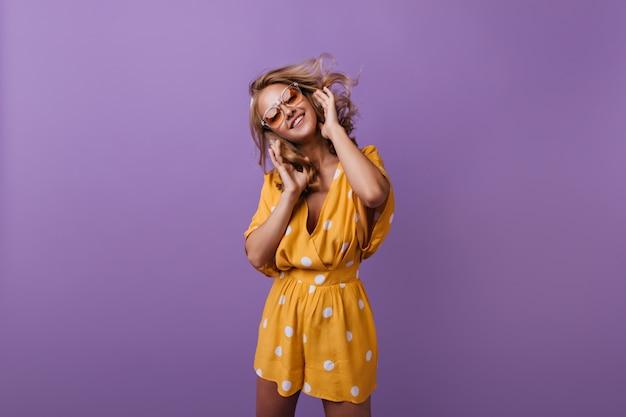 Charmante lachende frau tanzen. debonair gebräuntes mädchen in der orange kleidung, die auf lila lächelt.