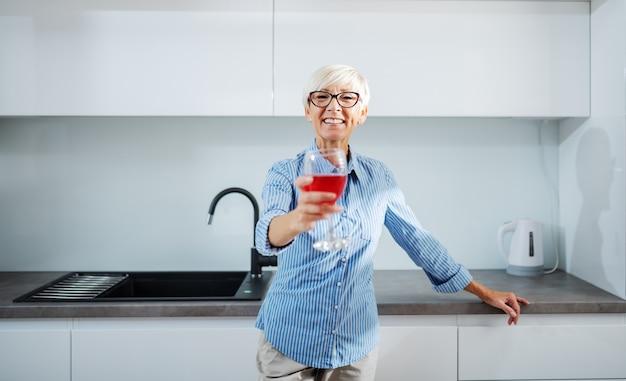 Charmante lächelnde ältere blonde frau, die sich auf küchentheke stützt und glas rotwein hält