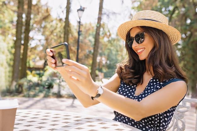 Charmante lächelnde dame, die selfie im sonnigen warmen tag macht