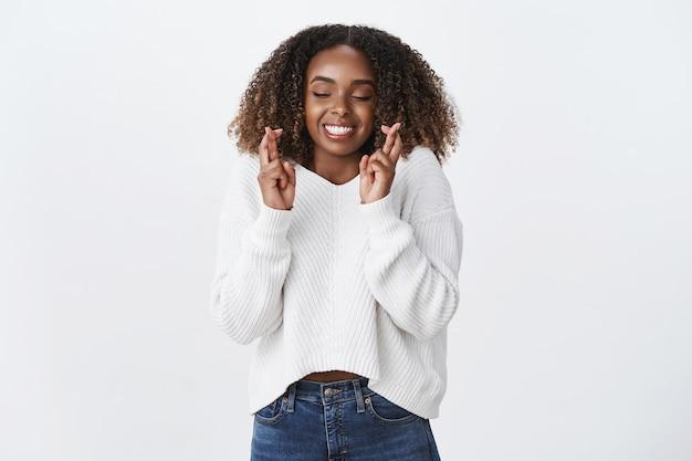 Charmante lächelnde glückliche afroamerikanische junge frau, die die finger kreuzt, viel glück, geschlossene augen, die gerne lächeln, machen die wunschtraumparty gut, weiße wand