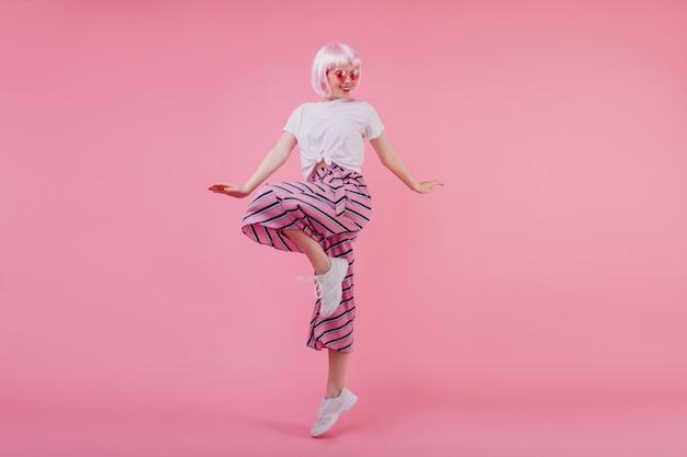 Charmante lächelnde junge dame im kurzen peruke tanzen. innenporträt der attraktiven frau in der rosa perücke, die auf einem bein aufwirft