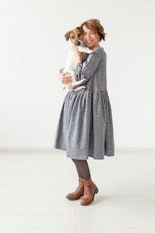 Charmante lächelnde junge frau in einem stilvollen grauen kleid, das ihren lieblingshund jack russell terrier hält