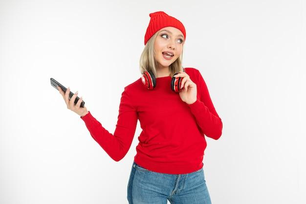 Charmante lächelnde junge frau in roten kleidern mit kopfhörern und einem telefon auf einem weißen studiohintergrund.