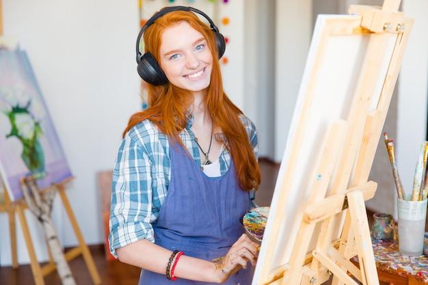 Charmante lächelnde junge künstlerin in kopfhörern und schürze, die auf leinwand malt und musik im kunststudio hört