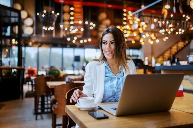Charmante lächelnde kaukasische brünette, die im café sitzt und sich darauf vorbereitet, online zu arbeiten.