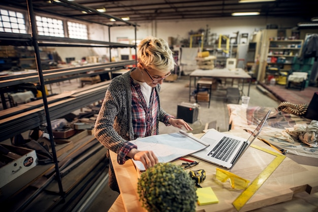 Charmante lächelnde motivierte ingenieurin mit kurzen haaren und brillen, die mit blaupausen und laptop in der werkstatt arbeiten