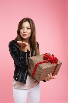 Charmante langhaarige frau, die kuss bläst, gerade schaut und geschenk hält