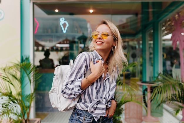 Charmante liebenswerte frau mit blonden haaren, die mit rucksack im äußeren fotoshooting aufwirft