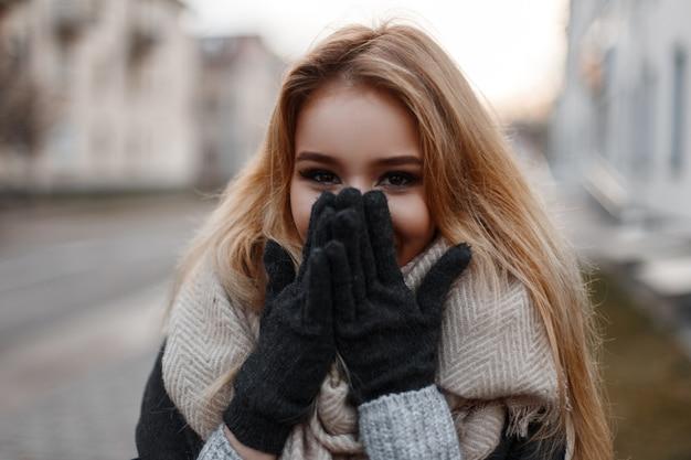 Charmante lustige junge frau mit schönen augen lacht und bedeckt ihr gesicht mit den händen. fröhliches stilvolles mädchen.