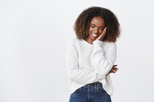 Charmante lustige sorglose afroamerikanerin lockige frisur lachen errötend süßer blick nach unten kichernd flirty touch wange mit spaß gute laune, scherzend humorvolle konversation, weiße wand